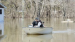 Two men use a small boat to navigate floodwaters on a residential street in the town of Rigaud, Que, west of Montreal, Monday, April 22, 2019. THE CANADIAN PRESS/Graham Hughes