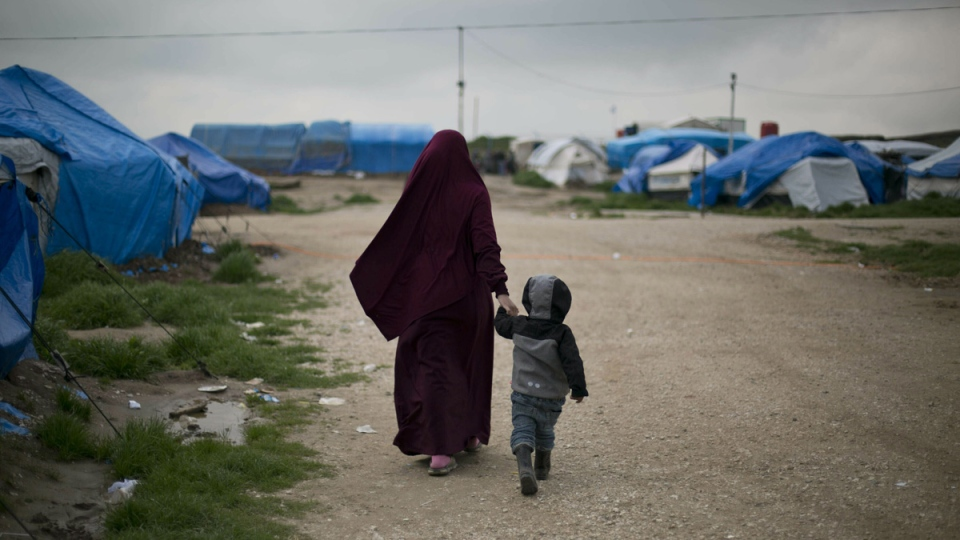 Samira from Belgium walks with her son at Camp Roj in north Syria, on March 27, 2019.  (Maya Alleruzzo / AP)
