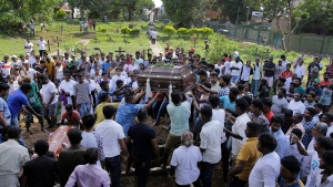 Sri Lankans prepare to bury the coffins carrying remains of Berington Joseph, left, and Burlington Bevon, who were killed in the Easter Sunday bombings in Colombo, Sri Lanka, Tuesday, April 23, 2019. (AP Photo/Eranga Jayawardena)