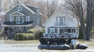 Members of the Naval Reserve patrol the Ottawa River next to homes surrounded by floodwaters in the town of Rigaud, Que, west of Montreal, Monday, April 22, 2019. THE CANADIAN PRESS/Graham Hughes