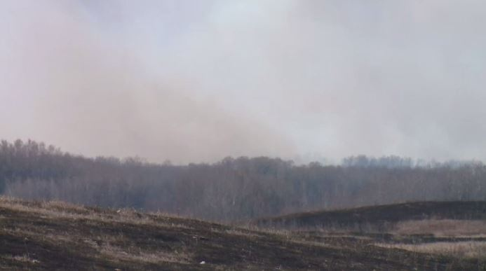 Scorched grass and smoke from the fire near Bigger.