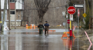 Local residents make their way through flood waters in Gatineau, Que., Tuesday, April 23, 2019. THE CANADIAN PRESS/Adrian Wyld
