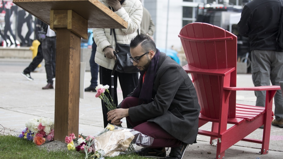 Omar Hassan arranges flowers left at a plaque in Toronto's Mel Lastman Square on Tuesday, April 23, 2019 to commemorate last year's van attack which left 10 people dead. Hassan maintained a makeshift memorial for 40 days after the attack. THE CANADIAN PRESS/Chris Young