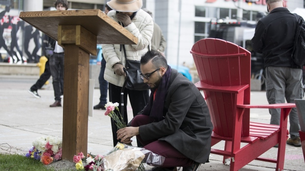 Omar Hassan arranges flowers left at a plaque in Toronto's Mel Lastman Square on Tuesday, April 23, 2019 to commemorate last year's van attack which left 10 people dead. Hassan maintained a makeshift memorial for 40 days after the attack. (The Canadian Press / Chris Young)