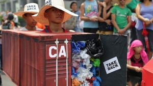 Filipino environmental activists wear a mock container vans filled with garbage to symbolize the 50 containers of waste that were shipped from Canada to the Philippines two years ago, as they hold a protest outside the Canadian embassy at the financial district of Makati, south of Manila, Philippines on May 7, 2015.  THE CANADIAN PRESS/AP, Aaron Favila