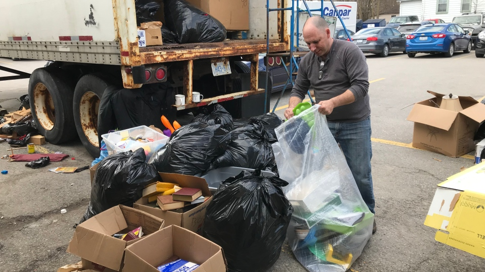 A volunteer cleans up a donation disaster from the back of the Salvation Army in Barrie on Tues., April 23, 2019 (CTV News/Aileen Doyle)