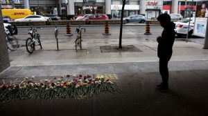 A woman stops to pay her respect at a makeshift memorial to one of the victims being remembered on Tuesday, April 23, 2019 ahead of a vigil held at in Toronto's Mel Lastman Square, to commemorate the 10 victims of last year's van attack. (THE CANADIAN PRESS/Chris Young)