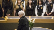 A flower is left to mark the memory of Dorothy Sewell, as 10 flowers, one for each victim, is placed in a vase during a memorial ceremony held in a civic centre in Toronto's Mel Lastman Square, on Tuesday, April 23, 2019, to commemorate last year's van attack which left 10 people dead. (THE CANADIAN PRESS/Chris Young)