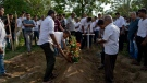 A mourner places flowers on a grave during a funeral of Easter Sunday suicide bomb blast victim at Methodist cemetery in Negombo, Sri Lanka, Tuesday, April 23, 2019. (AP Photo/Gemunu Amarasinghe)