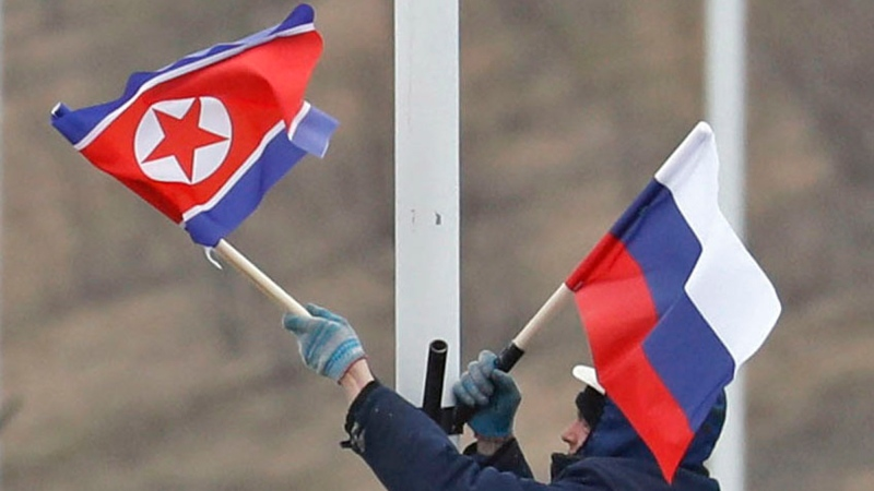 A worker adjusts the flag of Russia and North Korea along the road in Russky Island, off the southern tip of Vladivostok, Tuesday, April. 23, 2019. (Naoya Osato/Kyodo News via AP)