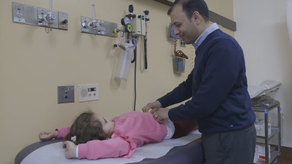 Julia's liver transplant surgeon Dr. Anand Ghanekar examines her during a check-up. (SickKids)