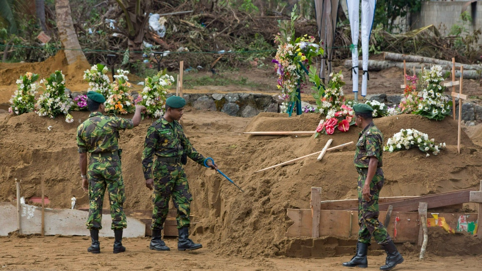 Officers of Special Task Force search for explosives ahead of mass burials at a burial ground for Easter Sunday bomb blast victims in Negombo, Sri Lanka, Wednesday, April 24, 2019. (AP Photo/Gemunu Amarasinghe)