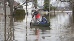 Stephen Kean and Laura Smith canoe from their home in Fredericton on Monday April 22, 2019. (THE CANADIAN PRESS/Stephen MacGillivray)