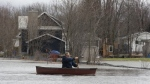 Mike Laurent paddles his canoe through floodwaters near homes in Gatineau, Que., Wednesday, April 24, 2019. THE CANADIAN PRESS/Adrian Wyld