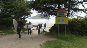 Surfers leave a Tofino beach as Lovekin Rock is viewed in the distance. (CTV Vancouver Island)