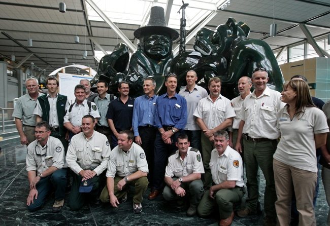 Firefighters from Australia and New Zealand gather for a photograph beneath a Bill Reid First Nations Haida Gwaii sculpture after arriving at Vancouver International Airport in Richmond, B.C., on Thursday August 6, 2009. (CP/Darryl Dyck)
