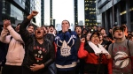 People watch the NBA Toronto Raptors and the NHL Maple Leafs on large outdoor screens in Maple Leaf Square in Toronto on Tuesday, April 23, 2019. (THE CANADIAN PRESS/Christopher Katsarov)