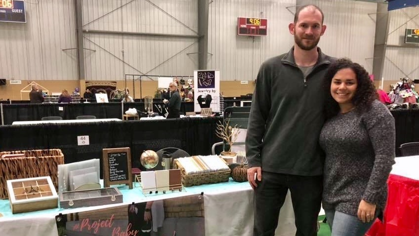 Craig and Tiz Sears in front of their trade show booth selling customizable notebooks. (Courtesy: Facebook)