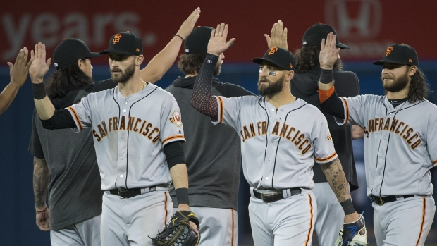 San Francisco Giants centre fielder Kevin Pillar, centre, celabrates with teammates after defeating the Toronto Blue Jays during ninth inning Interleague MLB baseball action in Toronto, on Wednesday, April 24, 2019. (THE CANADIAN PRESS/Nathan Denette)