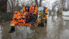 Residents get a lift on a tractor through the floodwaters Wednesday, April 24, 2019 in Laval, Que.THE CANADIAN PRESS/Ryan Remiorz