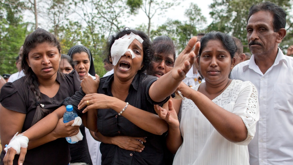 Anusha Kumari, center, weeps during a mass burial for her husband, two children and three siblings, all victims of Easter Sunday's bomb attacks, in Negombo, Sri Lanka, Wednesday, April 24, 2019. (AP Photo/Gemunu Amarasinghe)