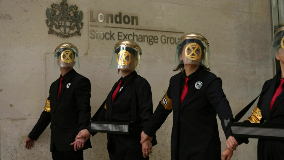 Extinction Rebellion climate protesters form a line after glueing themselves to the entrances of the London Stock Exchange in the City of London, Thursday April 25, 2019. (Isabel Infantes/PA via AP)
