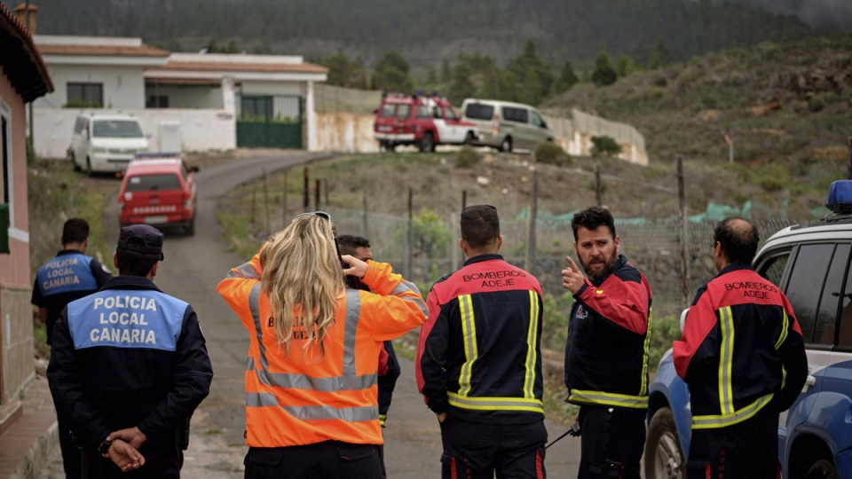 Members of an emergency team stand on a road leading to a cave at the base of the Teide volcano, on April 24, 2019. (Andres Gutierrez / AP)