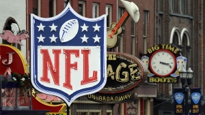 A temporary NFL neon sign joins the permanent ones along Broadway in Nashville, Tenn., on April 23, 2019. (Mark Humphrey / AP)