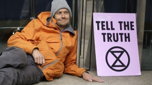An Extinction Rebellion climate change protester, his hand glued to the floor outside the London Stock Exchange, sits next to a placard on April 25, 2019. (Matt Dunham / AP)