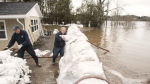 Terry Ferguson, right, gets help from friend Peter McMaster to stack sandbags around his Bay Street home to hopefully keep out the flood waters of the St. John River in Saint John, N.B., on Wednesday, April 24, 2019. THE CANADIAN PRESS/Stephen MacGillivray