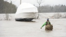 Mark Palmer wades through the flood waters of the St. John River after tying his brother's boat to the pole behind it so it wouldn't float away as the water continues to rise in Saint John, N.B., on Wednesday, April 24, 2019. (THE CANADIAN PRESS/Stephen MacGillivray)