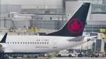 An Air Canada Boeing 737 Max 8 aircraft is shown next to a gate at Trudeau Airport in Montreal on March 13, 2019. Air Canada says it is removing its grounded Boeing 737 Max jets from service until at least Aug. 1 in order to provide more certainty for passengers with summer travel plans. THE CANADIAN PRESS/Graham Hughes
