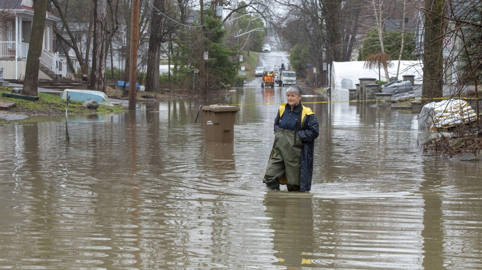 Michelle Belanger wades through floodwaters Wednesday, April 24, 2019 in Laval, Que. (THE CANADIAN PRESS/Ryan Remiorz)