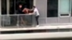 This frame is part of a video that shows a man walking along a narrow ledge connecting two balconies at a Toronto condo while holding a cat.