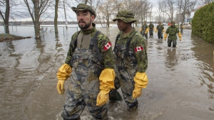 Canadian Forces personnel wade through the floodwaters Thursday, April 25, 2019 in Laval, Que. (THE CANADIAN PRESS / Ryan Remiorz)