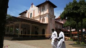 Sri Lankan Roman Catholic priests walk past damaged St. Sebastian's Church in Katuwapitiya village in Negombo, north of Colombo, Sri Lanka, Thursday, April 25, 2019. (AP Photo/Manish Swarup)