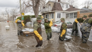 Canadian Forces personnel sandbag a house against the floodwaters in Laval, Que., on April 25, 2019. (Ryan Remiorz / THE CANADIAN PRESS)