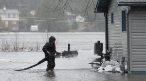 A resident works on his pump as flood waters surround his home on Friday, April 26, 2019 in Ottawa. THE CANADIAN PRESS/Adrian Wyld