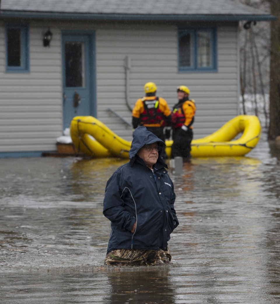 Paul Graveline makes his way through flooding waters outside his home Friday, April 26, 2019 in Ottawa. THE CANADIAN PRESS/Adrian Wyld