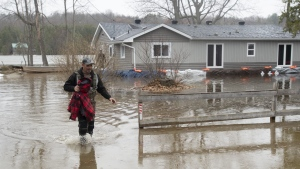 A man walks through flood waters around a home on Friday, April 26, 2019 in Ottawa. THE CANADIAN PRESS/Adrian Wyld