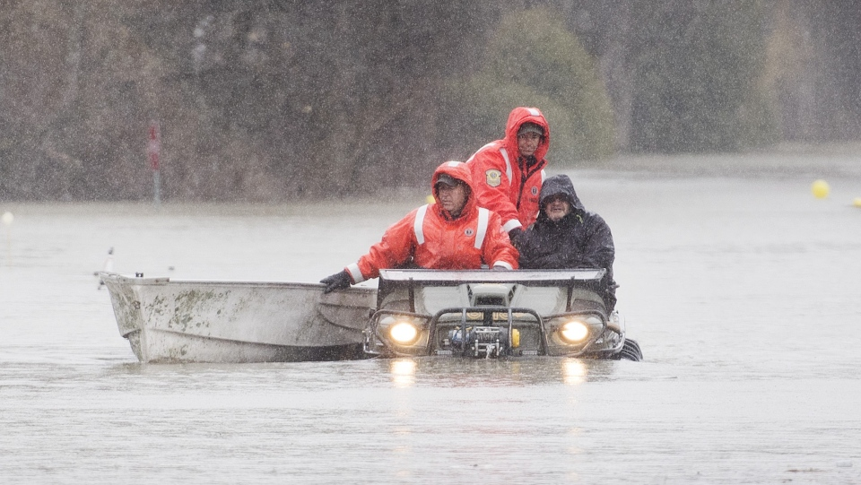 Members of the Surete du Quebec evacuate a man from his home in Rigaud, Que. west of Montreal, Friday, April 26, 2019. The town issued a mandatory evacuation order earlier Friday as floodwaters continue to rise. THE CANADIAN PRESS/Graham Hughes