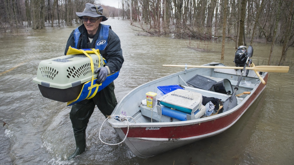 William Bradley removes a pet from a small boat next to a flooded street in Rigaud, Que, west of Montreal, Friday, April 26, 2019. THE CANADIAN PRESS/Graham Hughes