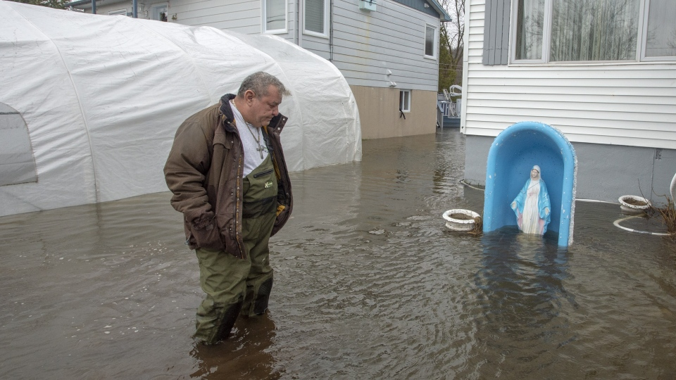 A resident surveys the flood waters surrounding his home Friday, April 26, 2019 in Lachute, Que. THE CANADIAN PRESS/Ryan Remiorz