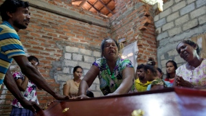 Lalitha, center, weeps over the coffin of her 12-year old niece, Sneha Savindi, who was a victim of the Easter Sunday bombing at St. Sebastian Church, after being brought home in Negombo, Sri Lanka, Monday, April 22, 2019. (AP Photo/Gemunu Amarasinghe)