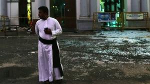 A Sri Lankan catholic priest stands near broken glass in front St. Anthony's Church in Colombo, Sri Lanka, Friday, April 26, 2019. (AP / Manish Swarup)