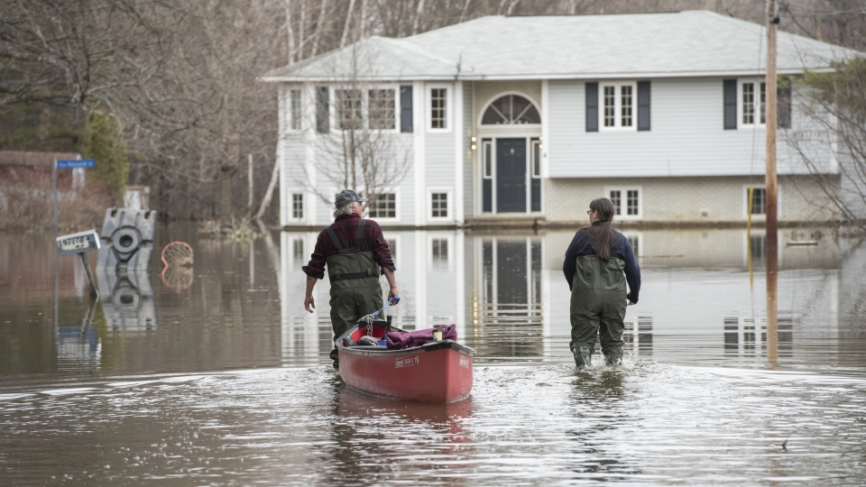 Keith McKay and Dee Branston use a canoe to carry food to a house on Jarvis Street in Fredericton, New Brunswick on Friday April 26, 2019. THE CANADIAN PRESS/Stephen MacGillivray