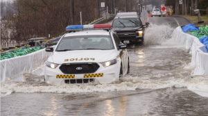 A police car leads the way through a flooded highway on Friday, April 26, 2019 in St.-Andre-D'Argenteuil, Que. THE CANADIAN PRESS/Ryan Remiorz