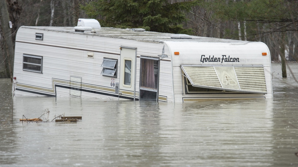 A mobile home is nearly covered with water in a flooded neighbourhood in Yamachiche , Que. on Friday, April 26, 2019. (The Canadian Press / Paul Chiasson)