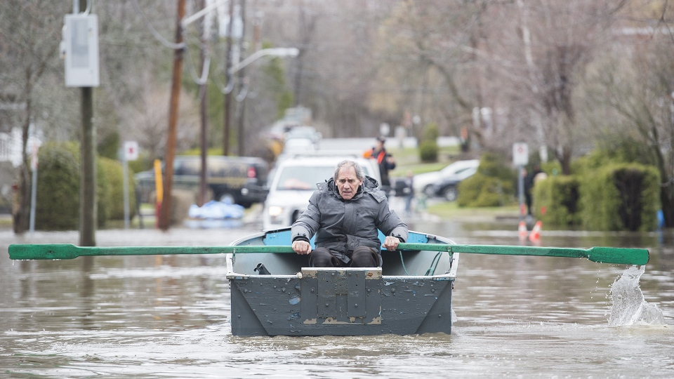 A man rows a small boat along a street surrounded by floodwaters on Ile Bizard west of Montreal, Saturday, April 27, 2019. (THE CANADIAN PRESS / Graham Hughes)