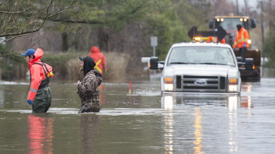 Volunteer emergency workers check on homes surrounded by floodwaters on Ile Bizard west of Montreal, Saturday, April 27, 2019. (THE CANADIAN PRESS / Graham Hughes)